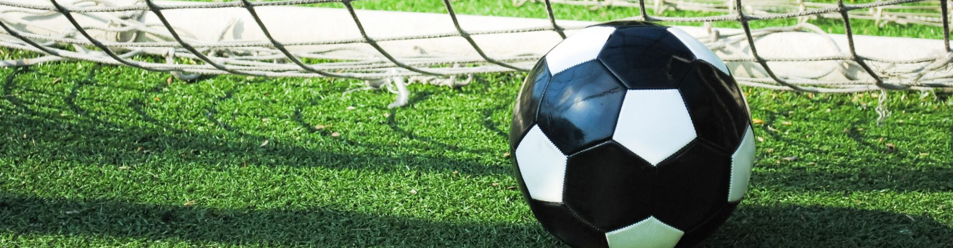 closeup-of-soccer-ball-in-the-goal-net-on-green-lawn